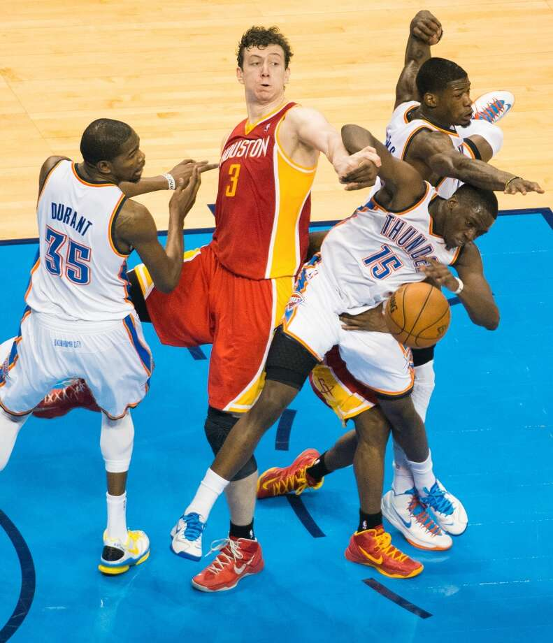 Rockets center Omer Asik and guard Aaron Brooks fight for a rebound with the Thunder's Kevin Durant, DeAndre Liggins and Reggie Jackson.