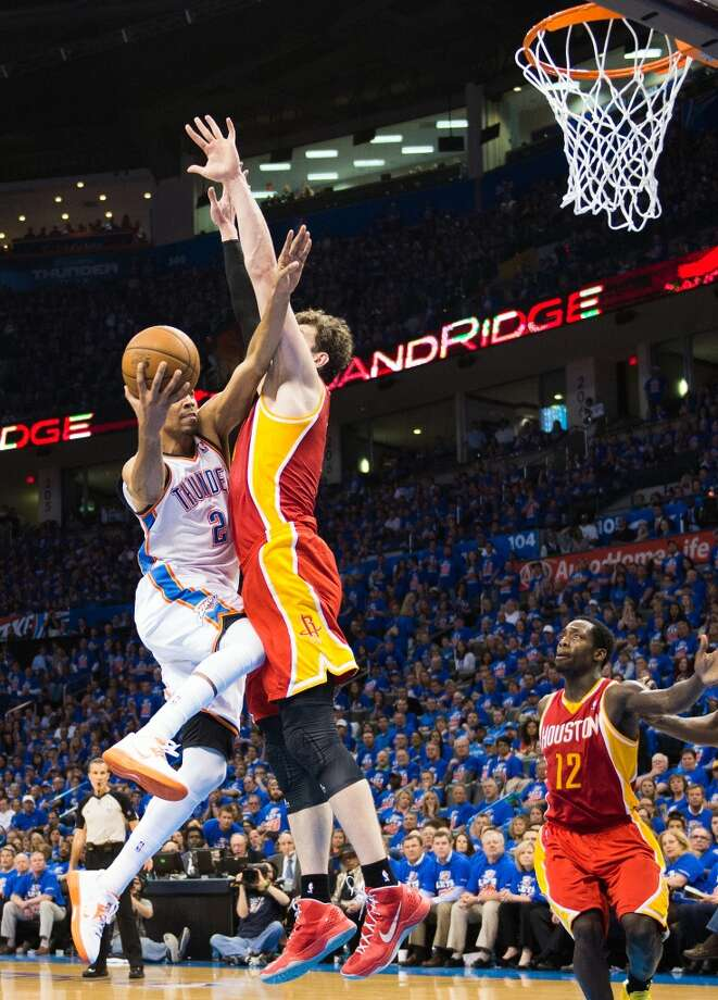 Rockets center Omer Asik defends a drive by Thunder shooting guard Thabo Sefolosha.