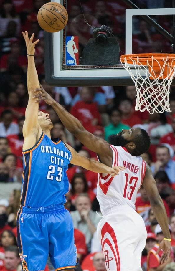 James Harden of the Rockets contests a shot from Thunder guard Kevin Martin.