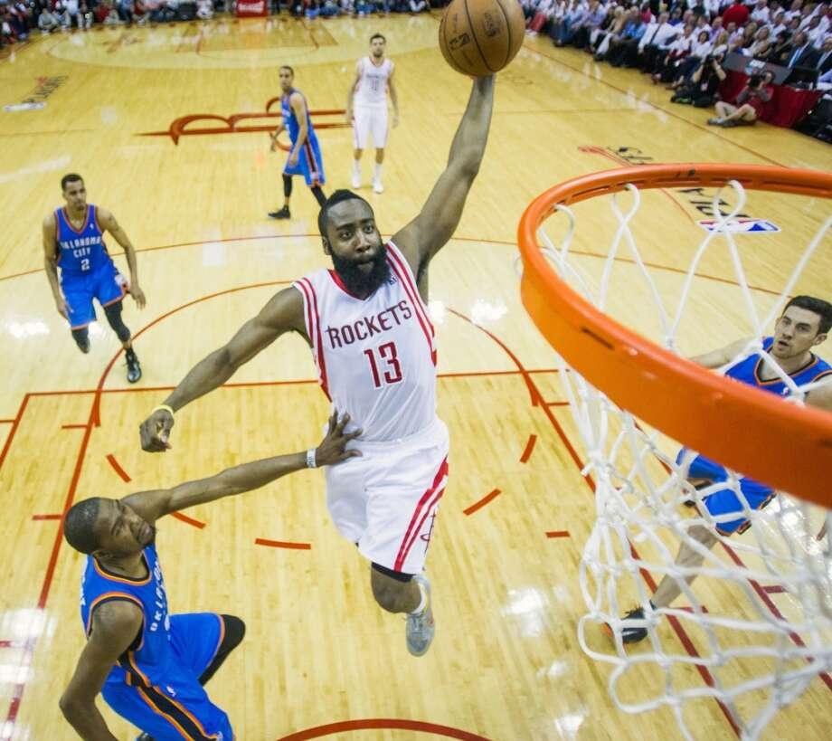 Rockets guard James Harden dunks past Thunder small forward Kevin Durant during the first half.