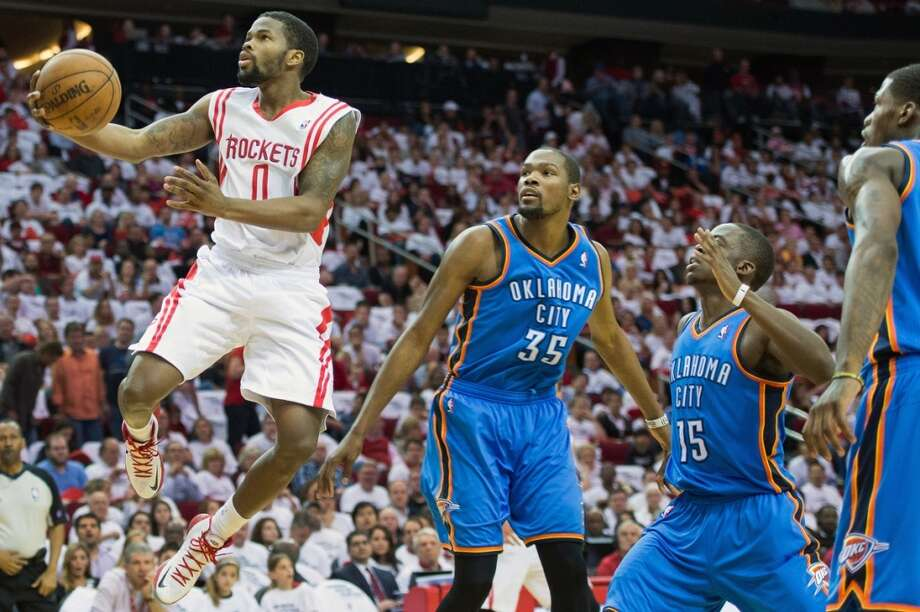 Rockets point guard Aaron Brooks drives to the basket past Thunder forward Kevin Durant and point guard Reggie Jackson.