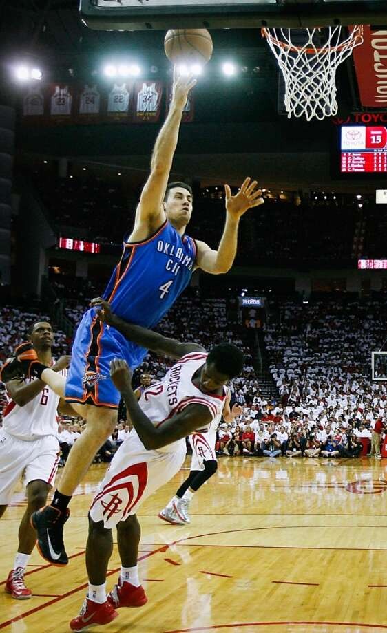 Thunder power forward Nick Collison shoots over Rockets point guard Patrick Beverley.