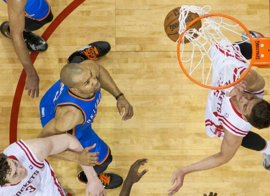 Rockets small forward Chandler Parsons dunks as Thunder point guard Derek Fisher looks on.