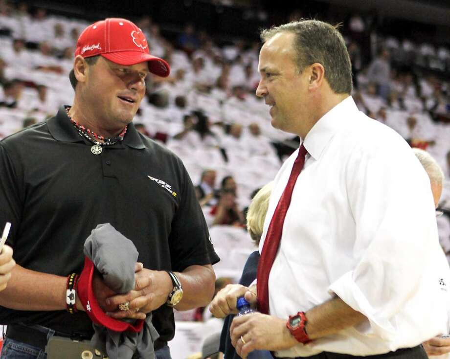 Former Houston Astros pitcher Roger Clemens left, and the Rockets CEO Tad Brown speak before the game.