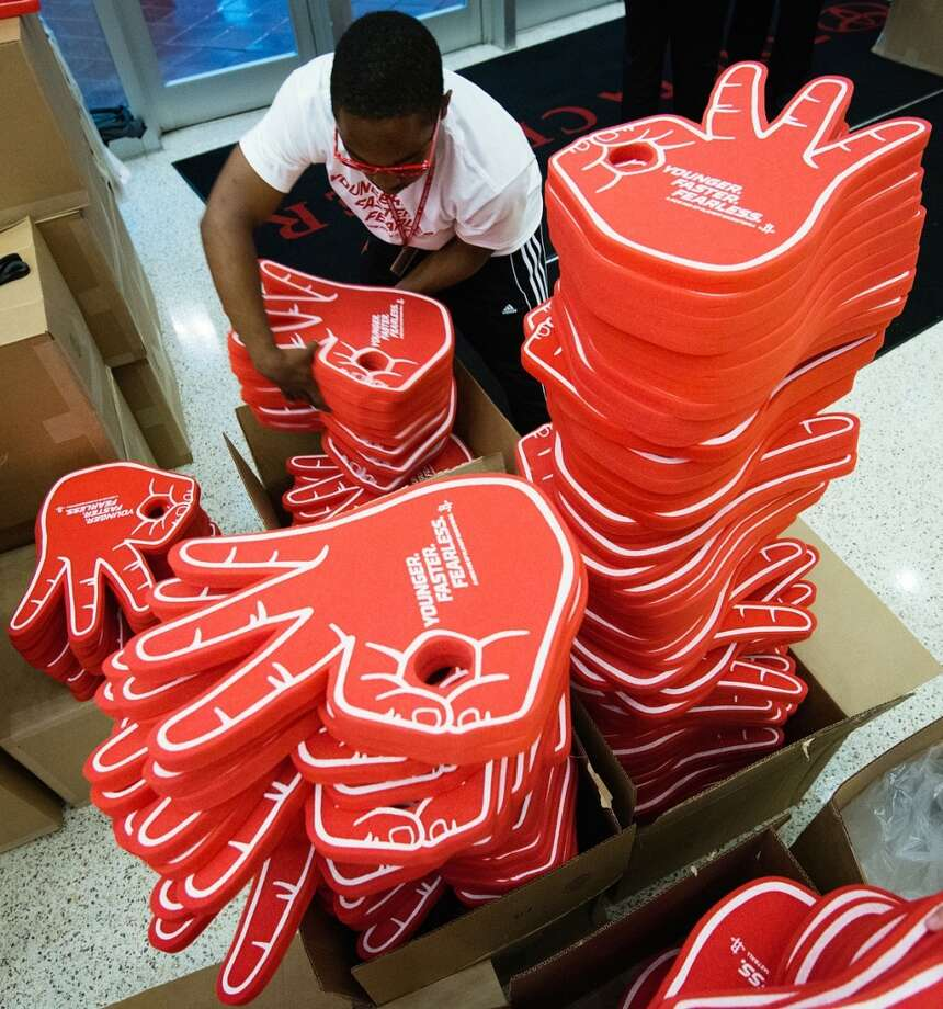 Workers prepare stacks of foam hands displaying a 3-point gesture to hand out to fans entering the arena.