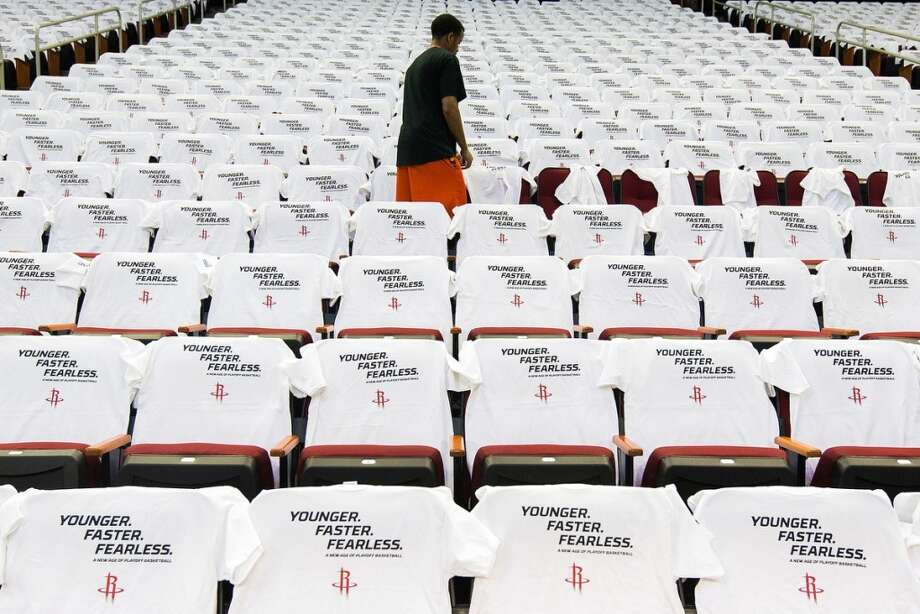 Workers cover the seats with Houston Rockets playoff t-shirts in preparation for Game 3.
