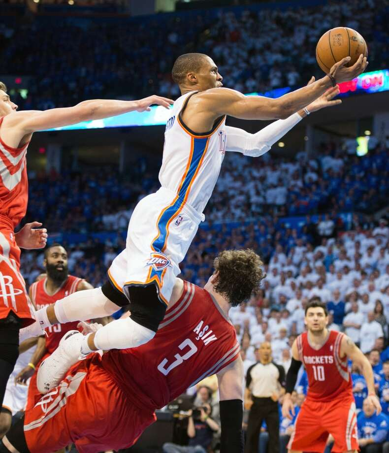 Thunder point guard Russell Westbrook drives over Rockets center Omer Asik (3), who was called for a foul on the play,during the second half.