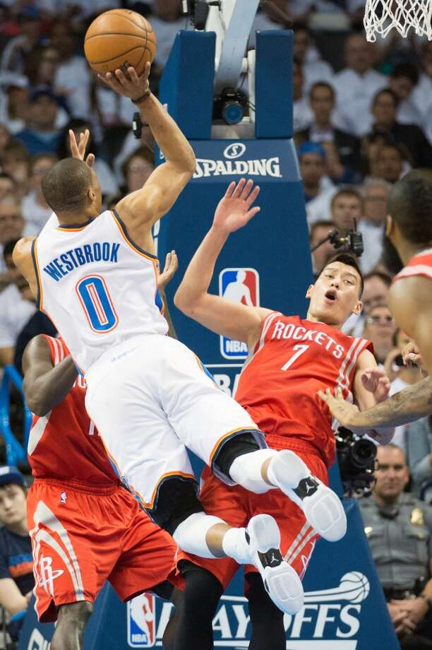 Rockets point guard Jeremy Lin (7) draws a charge on a drive by Thunder point guard Russell Westbrook.