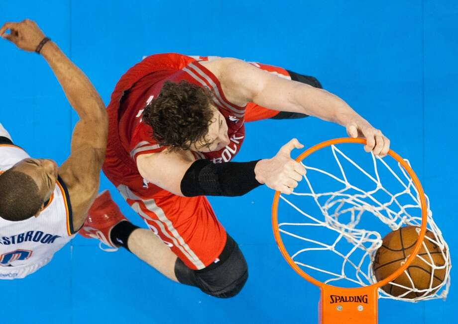 Rockets center Omer Asik dunks the ball past Thunder point guard Russell Westbrook.