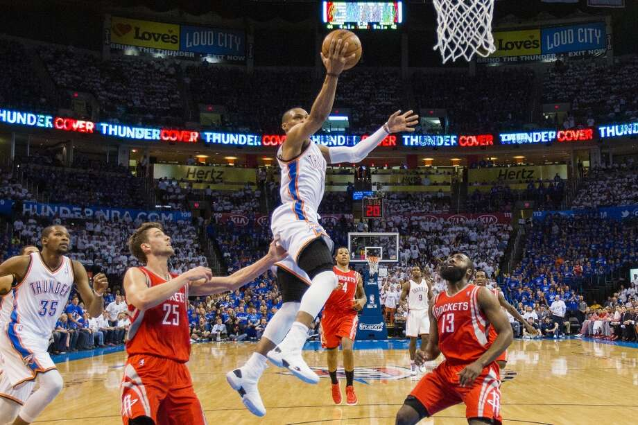 City Thunder point guard Russell Westbrook goes up for a layup past Rockets small forward Chandler Parsons (25) and shooting guard James Harden (13).