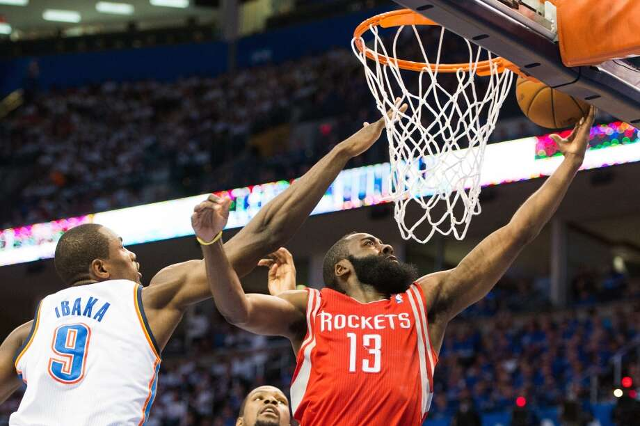 Rockets shooting guard James Harden drives to the basket past Thunder power forward Serge Ibaka during the first half.  Harden scored 36 points in the loss.