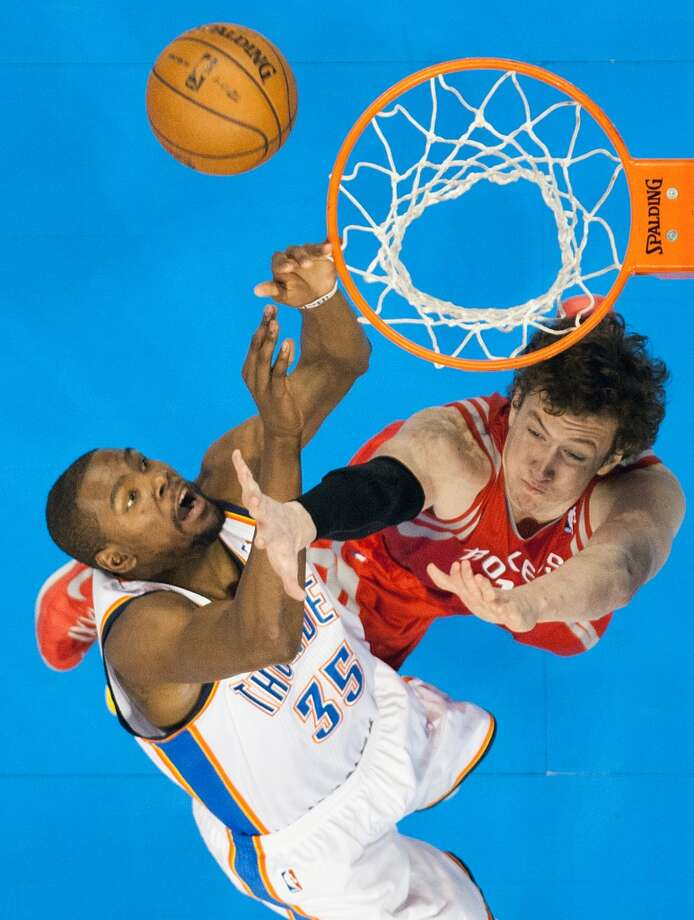 Rockets center Omer Asik gets tangled with Thunder small forward Kevin Durant during the first half.