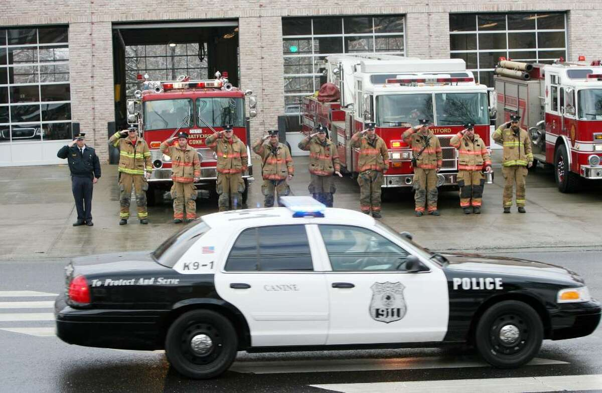 Stratford fire fighters salute a police procession as it passes headquarters on Main St. for Stratford K9 Officer Zak on Friday, Jan. 8, 2010. Stratford Fire, Police and K-9 partners from all over the state attended a service for Zak at the Birdseye Municipal Complex. His partner was Officer Thomas Clements.
