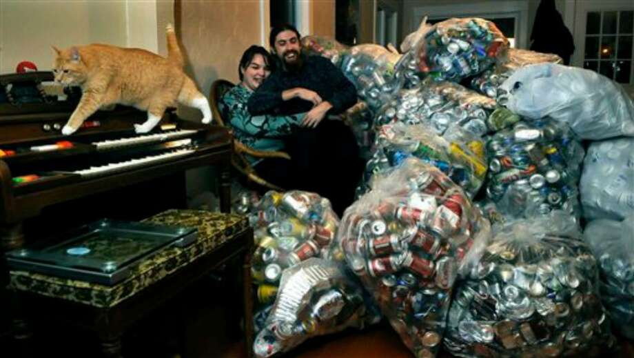 Andrea Parrish and Peter Geyer sit near some of the more than 18,000 aluminum cans they have collected to help pay for their wedding, Tuesday, Jan. 5, 2010, in Spokane, Wash. At left is their cat, Smudgie. Their goal is 400,000 cans to pay for their wedding.  (AP Photo/The Spokesman-Review, Dan Pelle) ** NO SALES  MAGS OUT  TV OUT  COEUR D'ALENE OUT ** Photo: Dan Pelle, AP / The Spokesman-Review