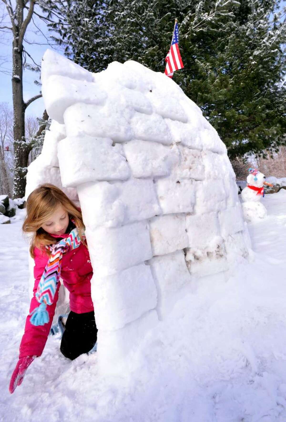 Ginger Kohanek, 6, works on a seven foot igloo she built with her dad, outside their Danbury home, on Friday, Jan.8,2010.