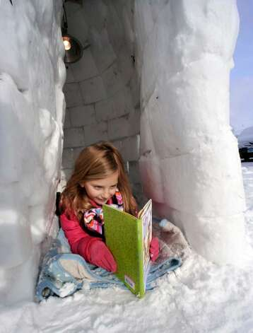 Ginger Kohanek, 6, reads a storybook inside a seven foot igloo she built with her dad, with a light inside, outside their Danbury home, on Friday, Jan.8,2010. Photo: Michael Duffy / The News-Times