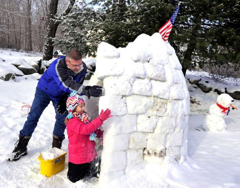 Steve Kohanek, and his daughter, Ginger, 6, work on a seven foot igloo they built outside their Danbury home, on Friday, Jan.8,2010. Photo: Michael Duffy / The News-Times