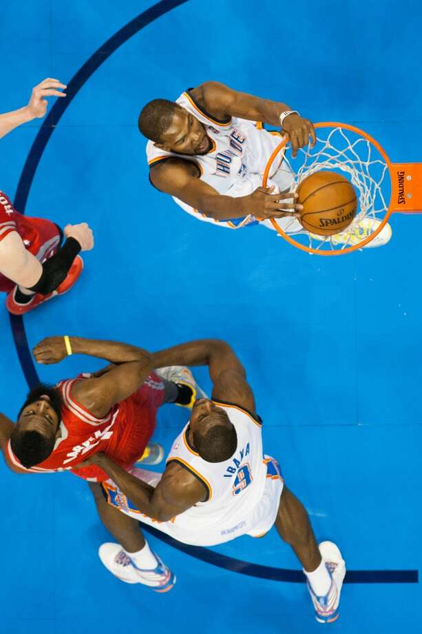 Thunder small forward Kevin Durant dunks as power forward Serge Ibaka (9) boxes out Houston Rockets shooting guard James Harden during the first half.