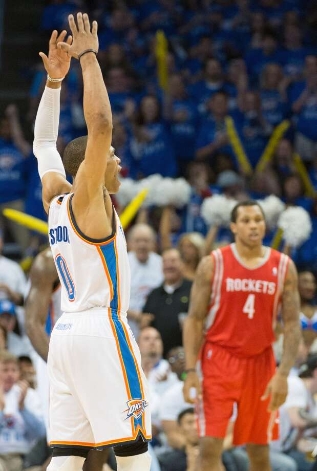 Thunder point guard Russell Westbrook celebrates after making a basket as Rockets power forward Greg Smith looks on.