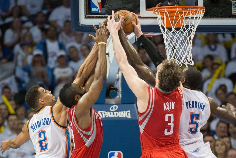 Oklahoma City guard Thabo Sefolosha (2) and center Kendrick Perkins (5) fight for a rebound against Rockets guard James Harden (13) and center Omer Asik (3).
