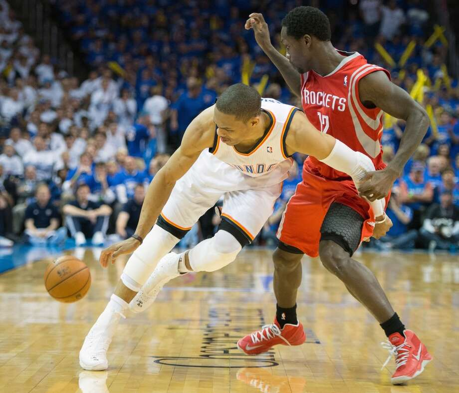 Thunder point guard Russell Westbrook turns the ball over as Rockets point guard Patrick Beverley defends during the second half.