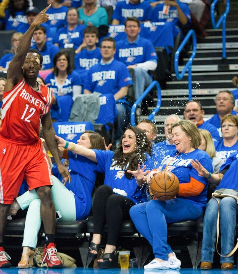 Rockets point guard Patrick Beverley looks for a favorable possession call as the ball splashes into a Thunder fan's beer.
