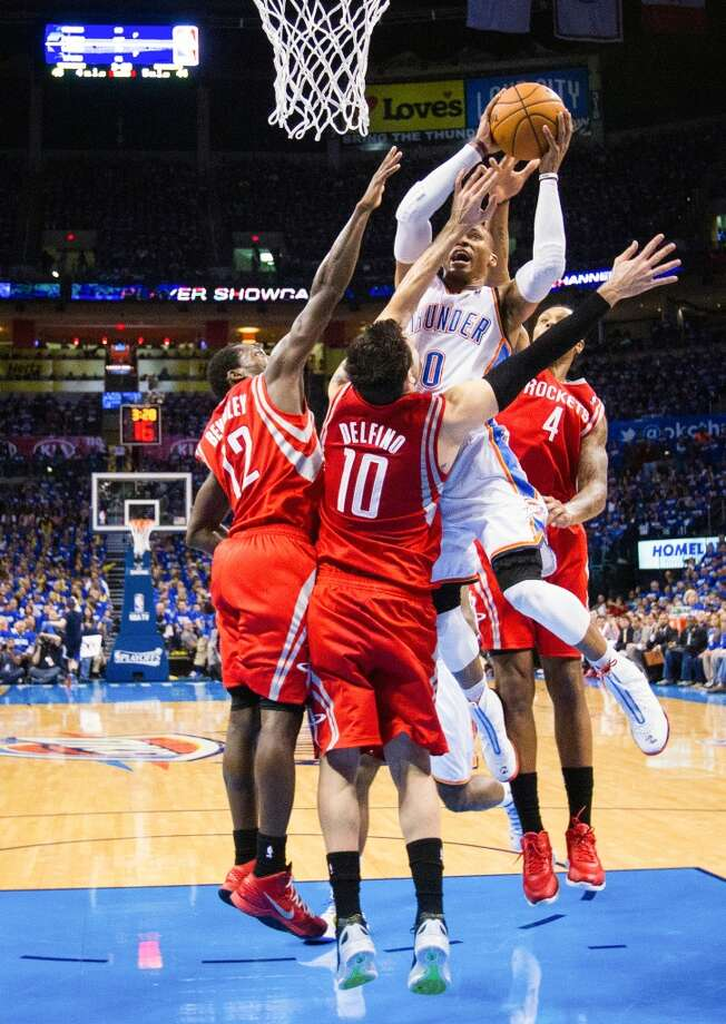 Thunder point guard Russell Westbrook (0) attracts a triple team from the Rockets Patrick Beverley (12), Carlos Delfino (10) and Greg Smith (4).
