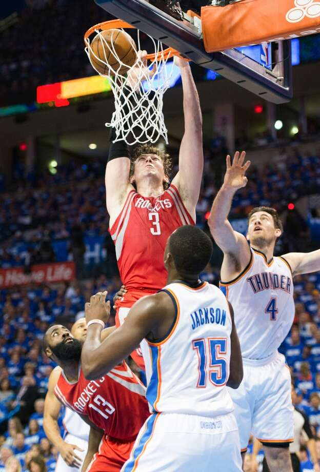 Rockets center Omer Asik (3) dunks the ball as Thunder point guard Reggie Jackson (15) and power forward Nick Collison (4) look on.