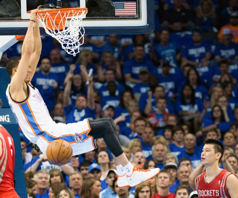 Thunder shooting guard Kevin Martin dunks the ball as Rockets point guard Jeremy Lin looks on.