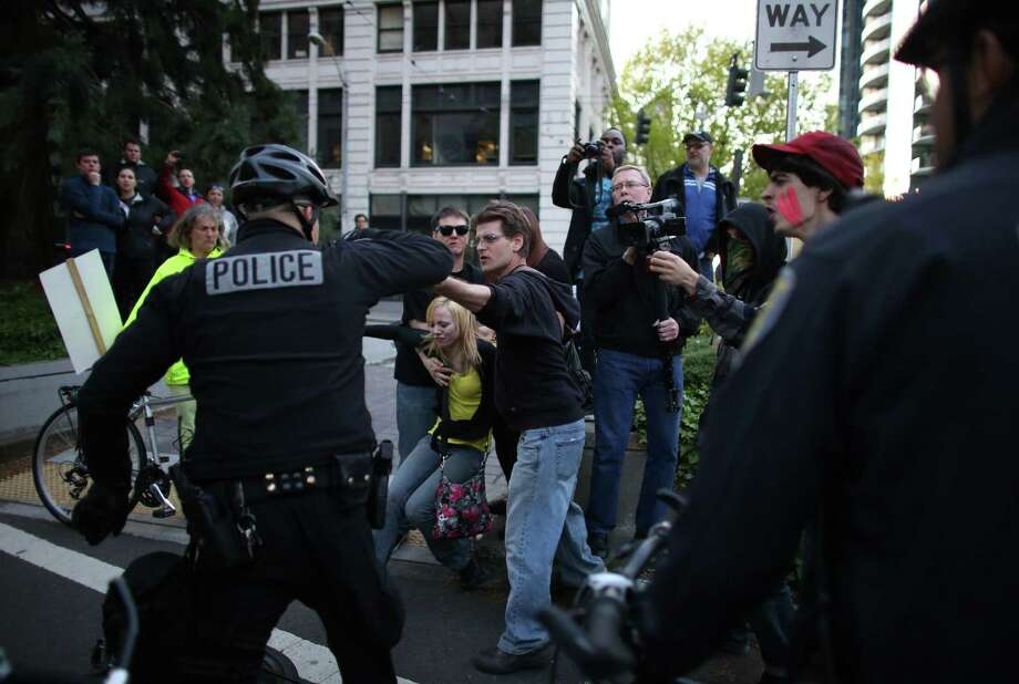 A woman, in yellow, falls after being shoved by an officer during a May Day march in downtown Seattle on Wednesday, May 1, 2013. Police aggressively responded to marchers as they blocked traffic and some threw objects at officers. Police responded with pepper spray and blast balls, firework-like devices that emit OC spray. Photo: JOSHUA TRUJILLO, SEATTLEPI.COM / SEATTLEPI.COM