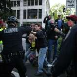 A woman, in yellow, falls after being shoved by an officer during a May Day march in downtown Seattle.