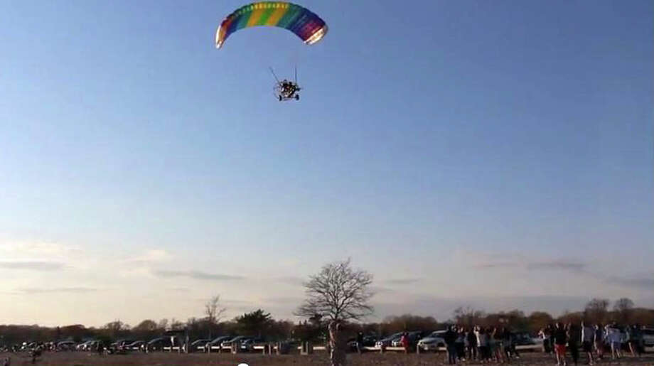 "Rich Ruggles delivers two Staples High School junior prom invitations with his ""powered parachute"" aircraft, as students look on at Compo Beach. Photo: Contributed Photo / Westport News contributed"