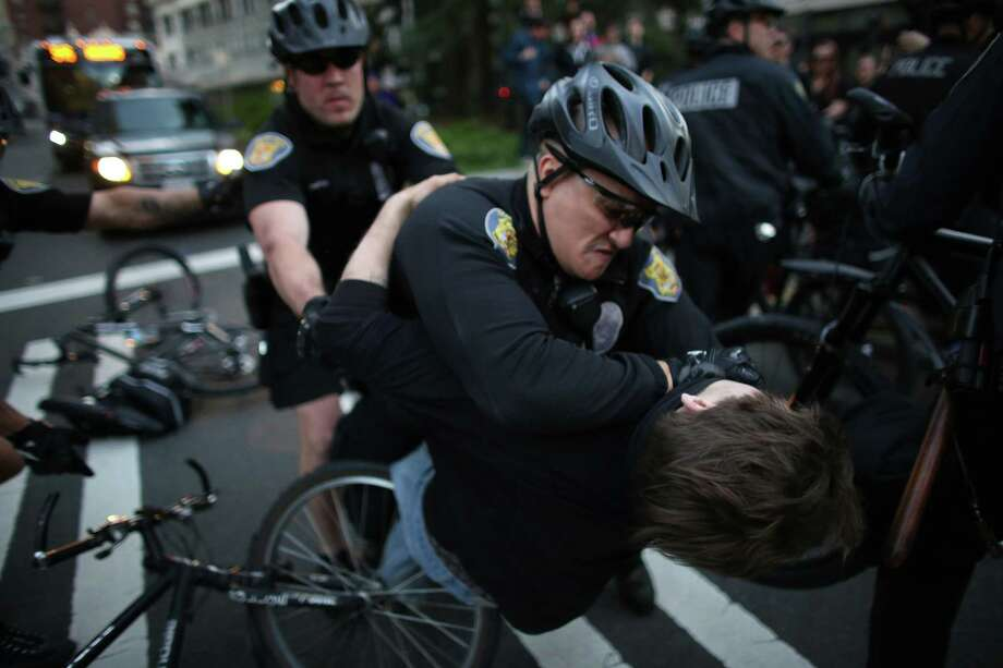 A man is taken down by officers after he scuffled with them when they  shoved a woman he was with during a May Day march in downtown Seattle. The man appeared to strike his head on the ground and was heard yelling for an ambulance. Photo: JOSHUA TRUJILLO, SEATTLEPI.COM / SEATTLEPI.COM