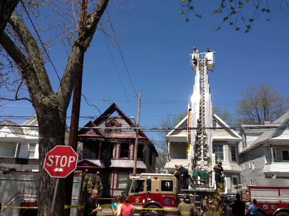 Schenectady firefighters raise the ladder above the scene of a fatal fire at 438 Hulett St. to photographs for their investigation into the fire's case. A man and three children died when the fire spread in their second-story apartment. (Paul Nelson / Times Union)