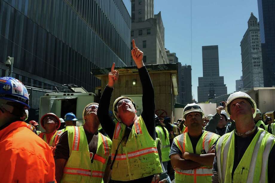 NEW YORK, NY - MAY 02:  Construction workers watch as the 408-foot spire is hoisted onto a temporary platform on the top of One World Trade Center on May 2, 2013 in New York City. When bolted into place at a later date, the spire will make One World Trade Center the tallest building in the Western Hemisphere.The raising of the spire, which comes on the second anniversary of the death of Osama bin Laden, will make One World Trade Center 1,776 feet tall. One World Trade Center is built on the site where the September 11, 2001 attacks toppled the original World Trade Center towers. Photo: Spencer Platt, Getty Images / 2013 Getty Images