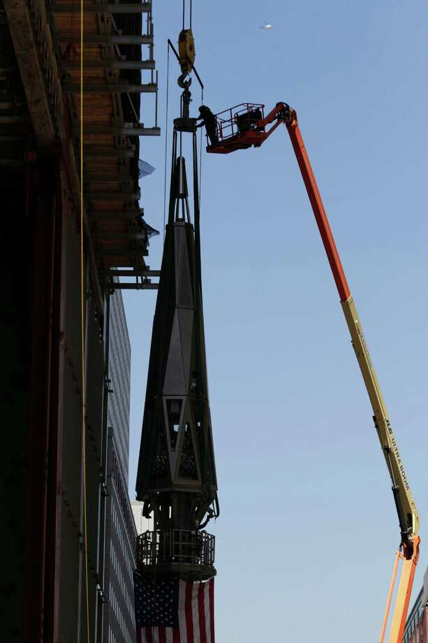 Workers attach a harness to the final piece of spire before it is hoisted to the roof of One World Trade Center, Thursday, May 2, 2013 in New York.  The piece will be attached to the spire at a later date, capping off the tower at 1,776 feet. Photo: Mark Lennihan, AP / AP