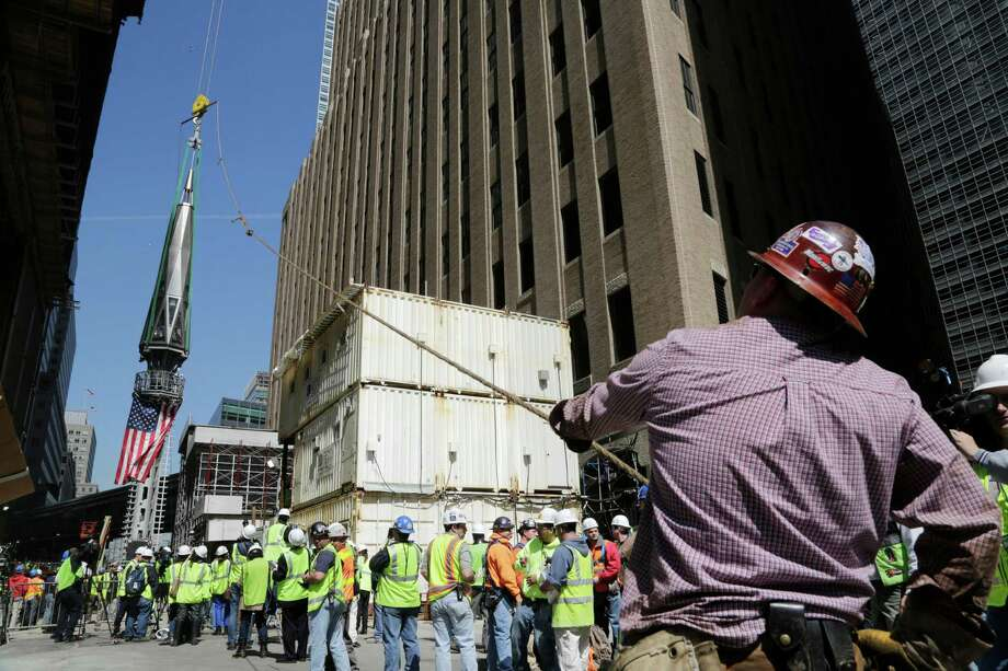 A worker holds a guide rope as the final piece of spire is hoisted to the roof of One World Trade Center, Thursday, May 2, 2013 in New York.  The piece will be attached to the spire at a later date, capping off the tower at 1,776 feet. Photo: Mark Lennihan, AP / AP
