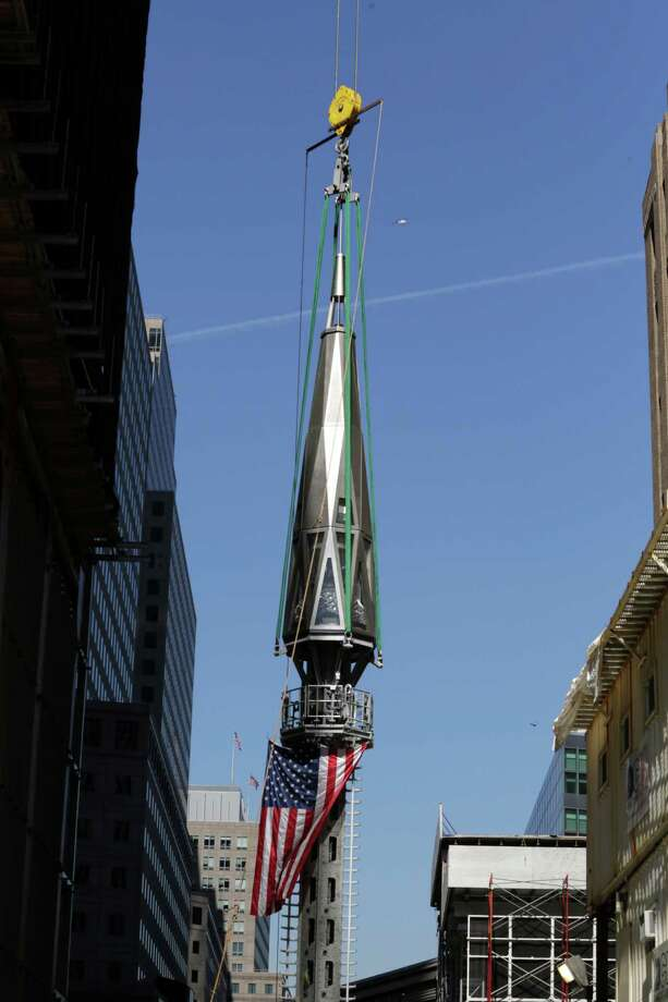 The final piece of the spire is hoisted to the roof of One World Trade Center, Thursday, May 2, 2013 in New York.  The piece will be attached to the spire at a later date, capping off the tower at 1,776 feet. Photo: Mark Lennihan, AP / AP
