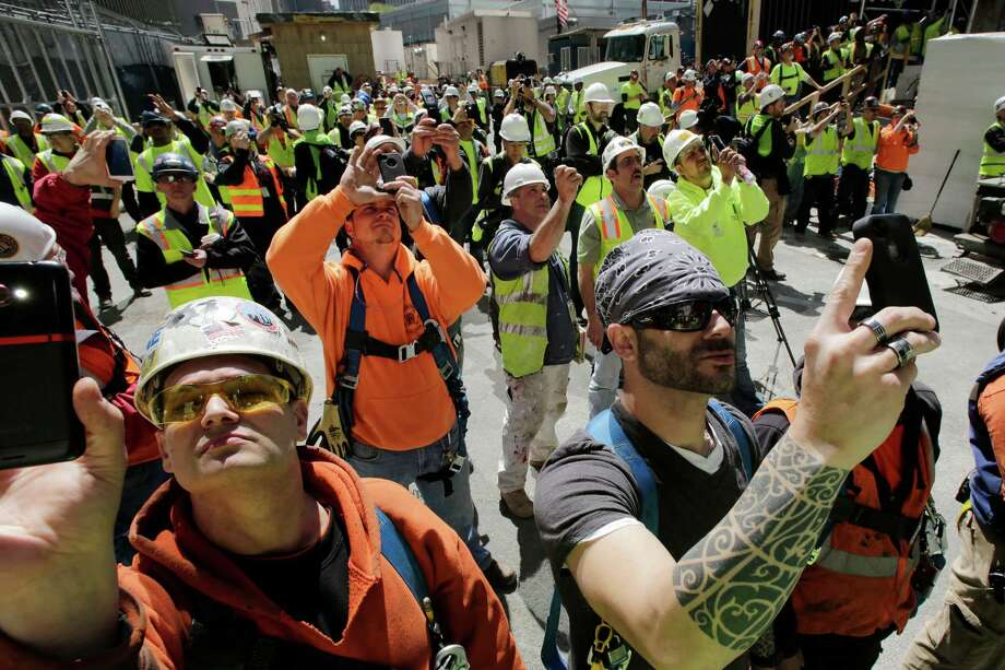Construction workers watch as the final piece of spire is hoisted to the roof of One World Trade Center, Thursday, May 2, 2013 in New York.  The piece will be attached to the spire at a later date, capping off the tower at 1,776 feet. Photo: Mark Lennihan, AP / AP