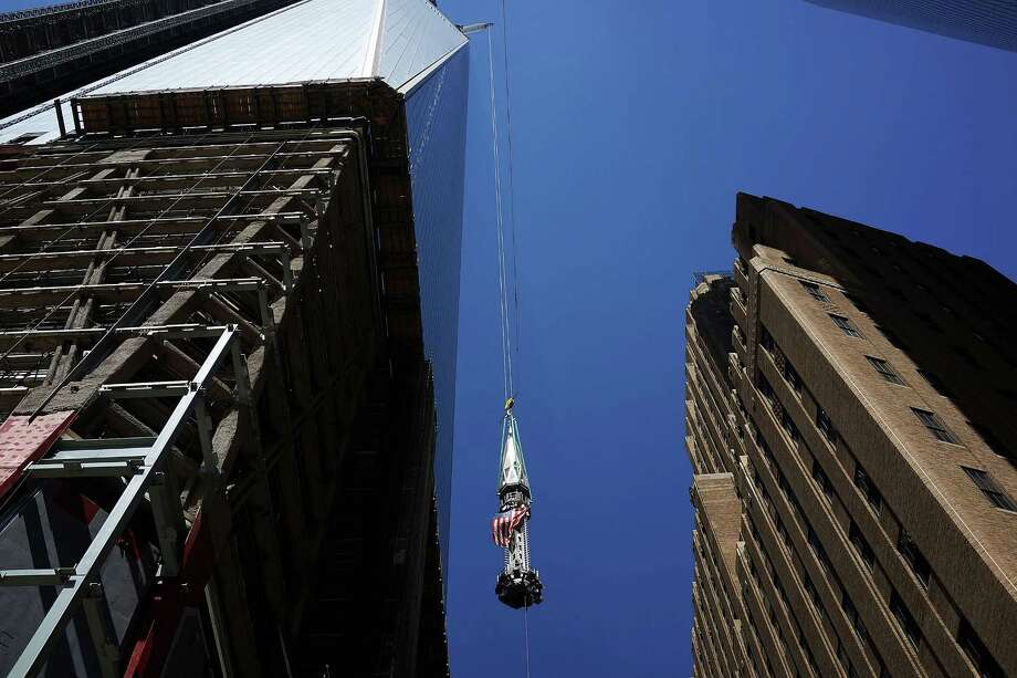 NEW YORK, NY - MAY 02: The 408-foot spire is viewed as it is hoisted onto a temporary platform on the top of One World Trade Center on May 2, 2013 in New York City. When bolted into place at a later date, the spire will make One World Trade Center the tallest building in the Western Hemisphere.The raising of the spire, which comes on the second anniversary of the death of Osama bin Laden, will make One World Trade Center 1,776 feet tall. One World Trade Center is built on the site where the September 11, 2001 attacks toppled the original World Trade Center towers. Photo: Spencer Platt, Getty Images / 2013 Getty Images