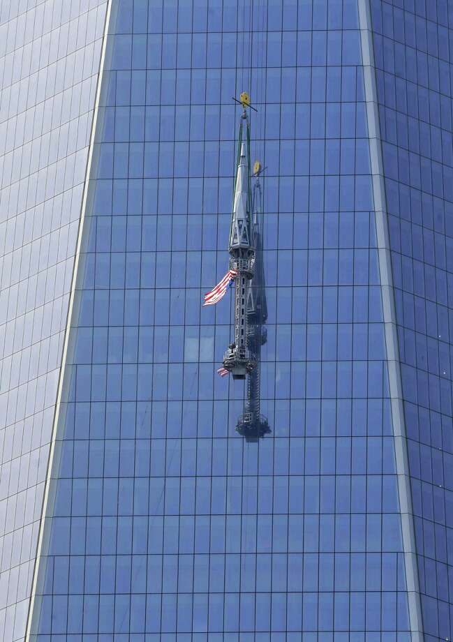 The top piece of the 408-foot spire for One World Trade Center is lifted to the top of the building in New York, Thursday, May 2, 2013. When it's fully installed, at a later date, it will top the building at a symbolic 1,776 feet. Photo: Seth Wenig, AP / AP