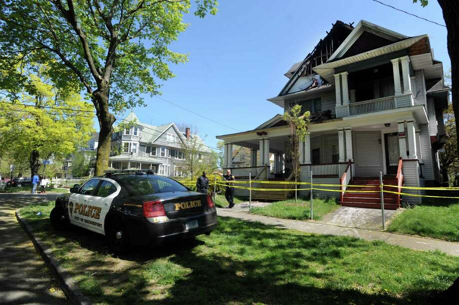 "Police stand outside a house on the corner of Park Ave. and Worth St. in Bridgeport, Conn. on Thursday, May 2, 2013.  The body of Robson Santos, was found inside a burned Park Avenue house late on Wednesday, May 1, 2013. Santos had visible signs of trauma, police said, and the case is being investigated as a ""possible homicide."" There may be a link between the fire that heavily damaged the third floor of the house at 1488-1490 Park Avenue, and a shooting nearby on Linen Avenue, police spokesman William Kaempffer said. Photo: Cathy Zuraw / Connecticut Post"