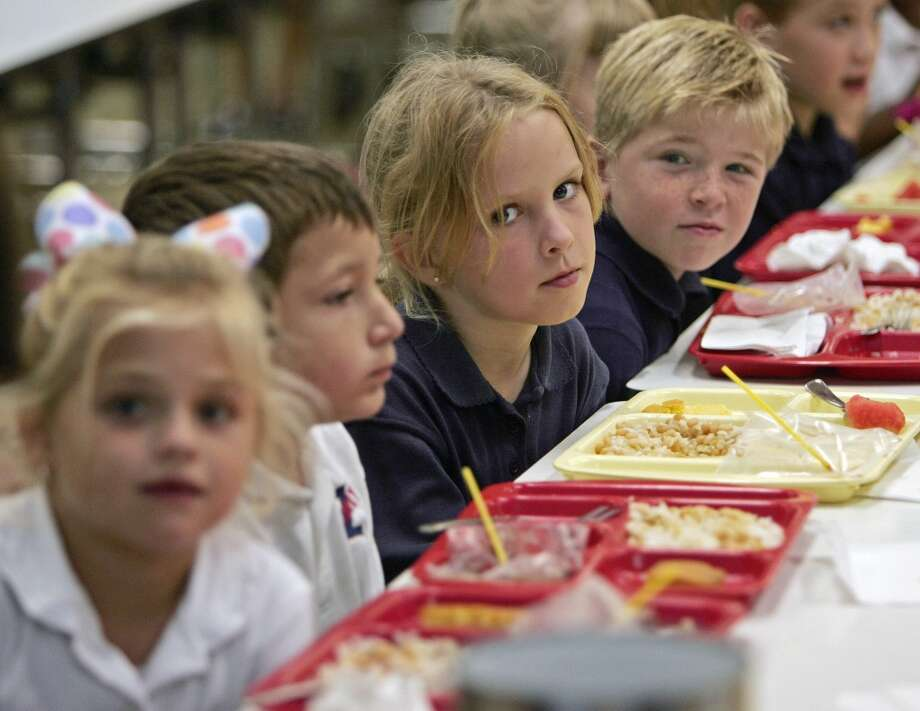 Children have lunch at Northwestern Elementary School 07 September 2005 in Zachary, Louisiana, where 75 children were accepted for the Fall 2005 school year after being displaced by Hurricane Katrina. School districts around the US are taking in hundreds of thousands of children who need to get back to school since their own schools were damaged or destroyed by Hurricane Katrina, the worst natural disaster in US history.       AFP Photo/PAUL J. RICHARDS  (Photo credit should read PAUL J.RICHARDS/AFP/Getty Images)