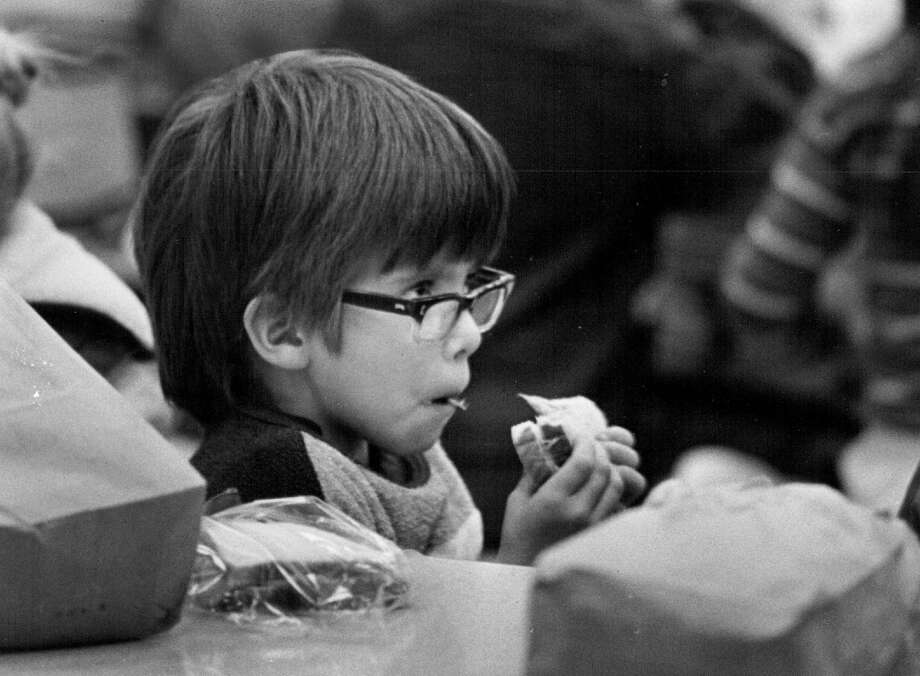 1982; Tommy Johnson, 7, eats a sandwich from the bag lunch he chose instead of the hot lunch offered in the cafeteria at Walnut Hills Elementary School. The bag lunches are part of a Cherry Creek School District pilot project.;  (Photo By Dave Buresh/The Denver Post via Getty Images)
