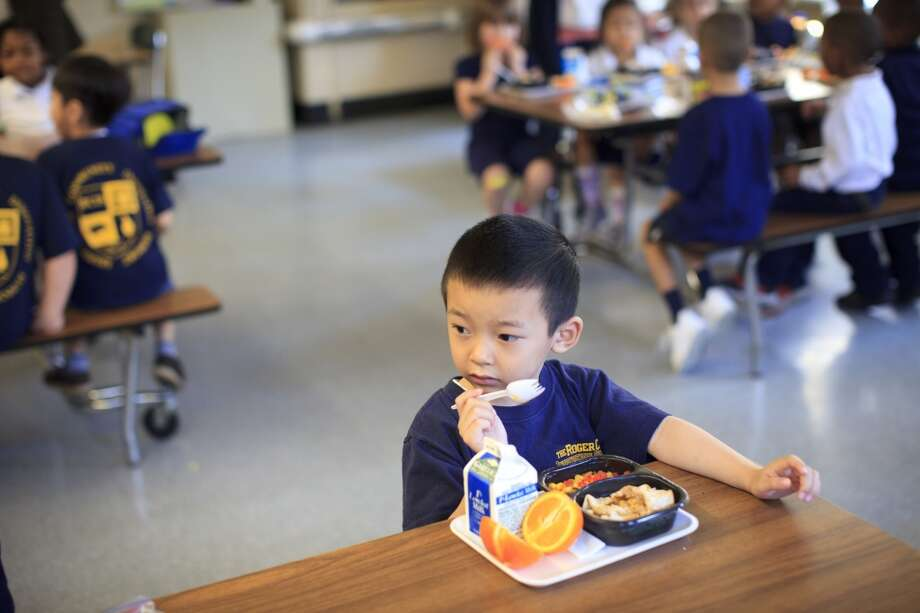 Trac Dzuong munched away at his lunch of soft tacos with a side of vegetables and an orange in Boston in 2012.(Photo by Dina Rudick/The Boston Globe via Getty Images)