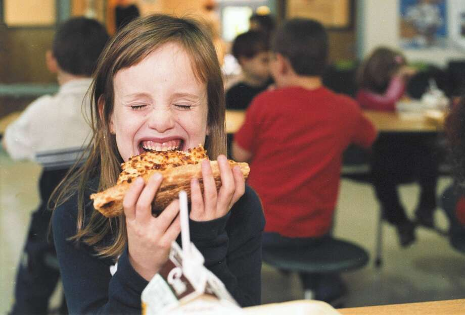 First grader Christina Muse takes a bite into a slice of pizza in the school cafeteria during lunch October 15, 2002 at North Hampton School in North Hampton, New Hampshire. North Hampton School has students from K through 8 and offer a balanced lunch menu everyday, some days even Dominos Pizza is even served.  (Photo by Debbi Morello/Getty Images)