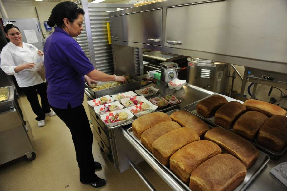 Each day head baker Colleen Garcia, in purple, bakes fresh bread and muffins for the school's breakfasts and lunches. (2012)