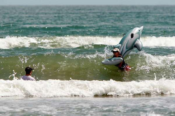 Nayeli Barrueta of Galveston hangs onto an inflatable dolphin while enjoying the water at Stewart Beach with her dad, Carlos Barrueta, shown left, and other family members and friends Friday, Sept. 3, 2010, Galveston.