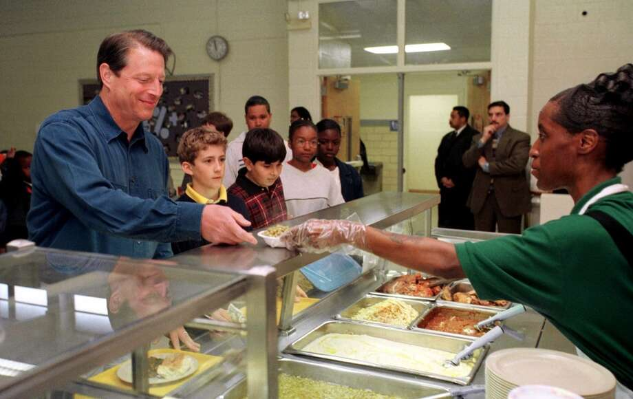 US Vice President and Democratic presidential candidate Al Gore gets his lunch from cafeteria worker Barbara Latta at Marie G. Davis Middle School during his 13 April, 2000, visit to the school in Charlotte, North Carolina.   AFP PHOTO  (Photo credit should read ERIK PEREL/AFP/Getty Images)