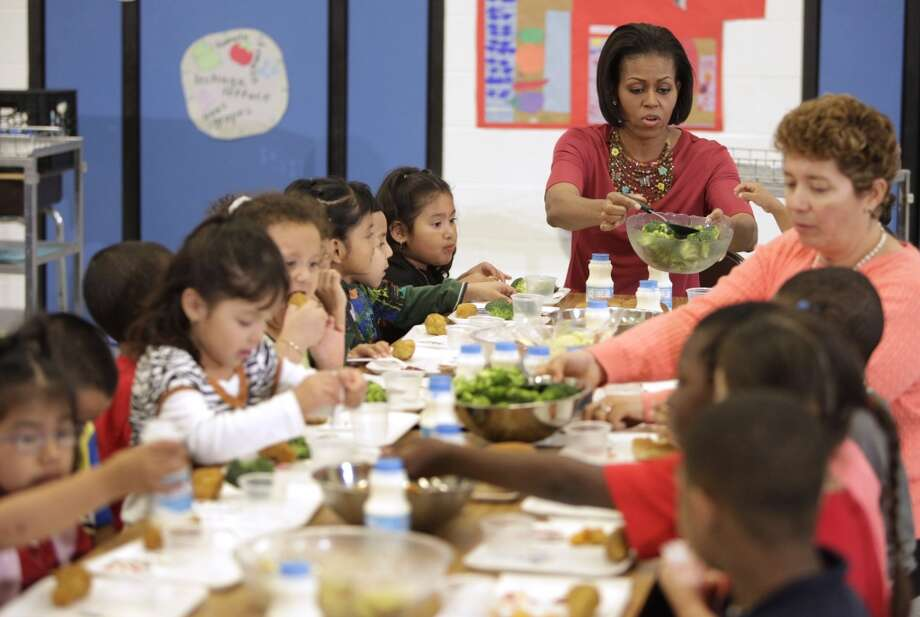 US First Lady Michelle Obama serves a broccoli to children during a lunch at New Hampshire Elementary School in Silver Spring, Maryland on May 19, 2010. (YURI GRIPAS/AFP/Getty Images)